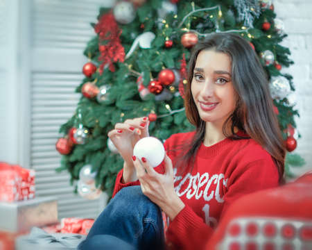 Happy young brunette female decorating christmas tree. Girl holding a christmas ball in her hands