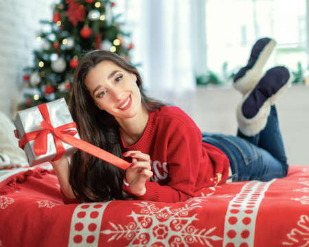 Happy young brunette female opening a gift box lying on bed in room with christmas tree