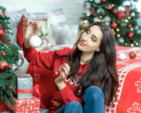 Happy young brunette female decorating christmas tree. Girl sitting and holding a christmas ball in her hands Stok Fotoğraf