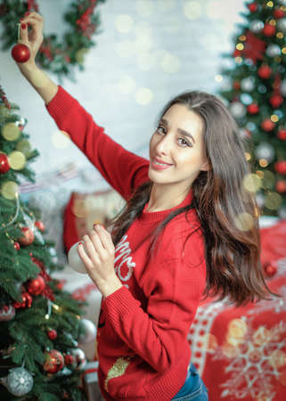 Happy young brunette female decorating christmas tree. Girl holding a christmas ball in her hands and looking into camera