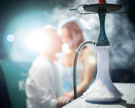 Blurred silhouette of young loving couple in hookah smoke. Man and woman smoking hookah
