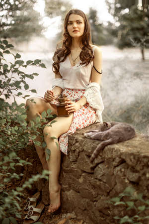 Retro style portrait of pretty young woman holding antique wooden coffee grinder and little gray kitten sleeping on stone fence in summer garden or yard Stok Fotoğraf