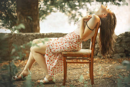 Retro or vintage style profile portrait of young pretty sad woman sitting on old wooden chair, holding paper letter to her chest in summer garden or yard.