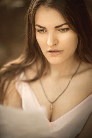 Retro style close-up portrait of a young pretty female reading paper letter.