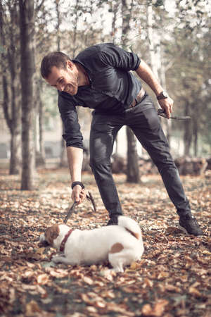 Portrait of young smiling man and cute purebred dog jack russell terrier playing with wooden stick together in autumn city park. Stok Fotoğraf