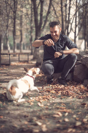 Portrait of young smiling man and cute barking purebred dog jack russell terrier playing together in autumn city park.