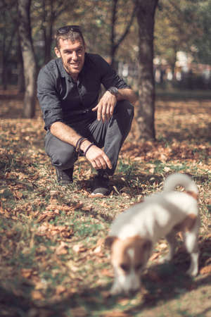 Portrait of young happy man and cute purebred dog jack russell terrier playing together in autumn city park. Stok Fotoğraf
