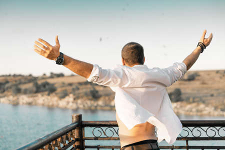 A portrait from the back of a man with his arms raised up against a background of sky and water. The man is wearing a white open shirt