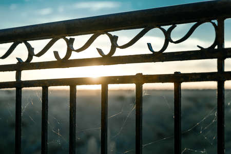 Old rusty metal fence or railing on beautiful bright abstract river sunset background.