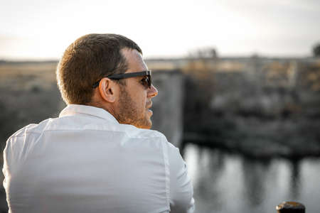 Portrait of young attractive man in white shirt and sunglasses looking at right against background of sky and water