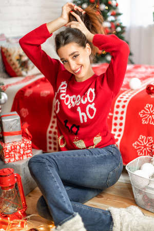 Portrait of happy young brunette female playing with her long hair in her bedroom decorated for christmas