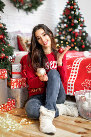Happy young brunette girl decorating christmas tree at her room. Female holding a christmas balls in her hands Stok Fotoğraf
