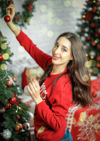 Portrait of happy young brunette female decorating christmas tree. Girl holding a christmas ball in her hands and looking into camera