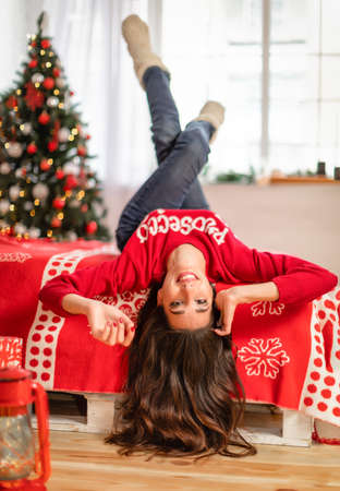 Portrait of happy young brunette female lying on bed in room with christmas tree near window. Stok Fotoğraf
