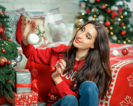 Close-up portrait of happy young brunette female decorating christmas tree. Girl sitting and holding a christmas ball in her hands
