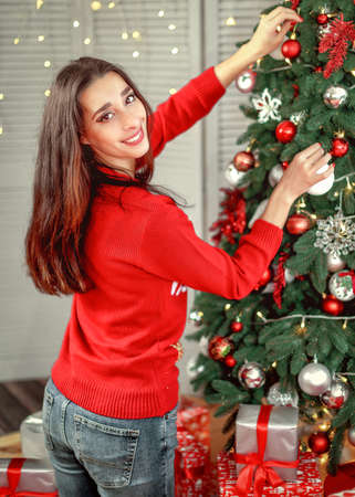 Portrait of happy young brunette female decorating christmas tree. Girl holding a christmas ball in her hands hanging on the tree Stok Fotoğraf