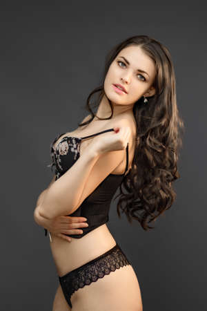 Portrait of a young beautiful girl with long dark hair posing in underwear on a black background