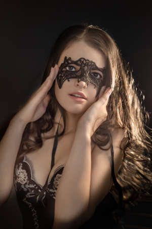 Portrait of a young beautiful sexy girl with long dark hair posing in underwear and a lace mask on her face on a black background. Stok Fotoğraf