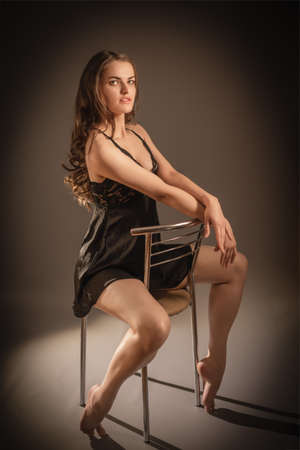 Portrait of a young beautiful girl with long dark hair posing in underwear sitting on a chair in studio