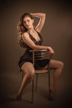 Portrait of a young beautiful girl touching her long dark hair posing in underwear sitting on a chair in studio Stok Fotoğraf