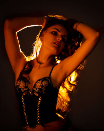 Bright portrait of a young beautiful woman with long dark hair on a black background with light