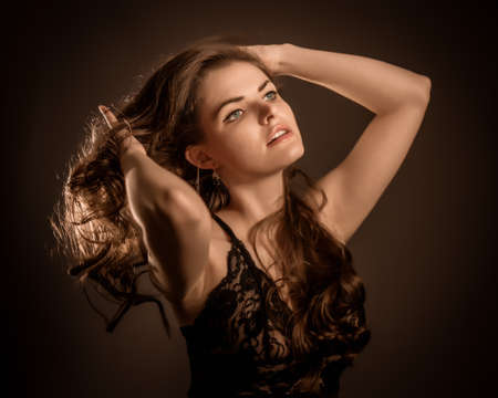 Close-up portrait of a young beautiful sexy girl playing with her long dark hair on a black background with light.