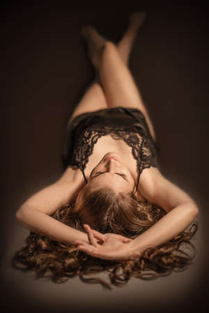 Portrait of a young beautiful sexy girl with long hair lying on dark background.