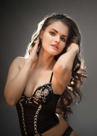 Close-up portrait of a young beautiful female with long dark hair posing in underwear and looking into camera on a black background with backlight Stok Fotoğraf