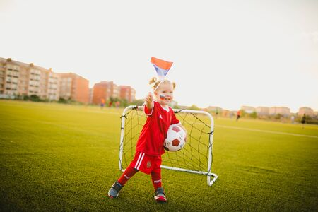 funny girl with two ponytails in red t-shirt waving russian flag and holding soccer ball on the background of a football goal on grass lawn