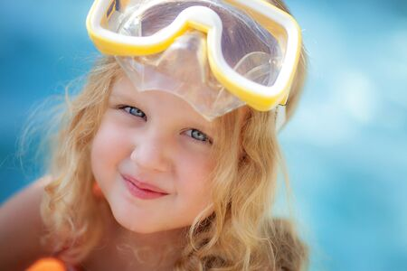 Little blonde girl with blue eyes in yellow swimming glasses sunbathing in the pool in the summer Reklamní fotografie