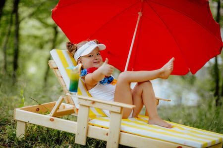 Funny little girl in white swimsuit with flowers relaxing on the striped yellow-and-white deck chair lounger with red sun umbrella