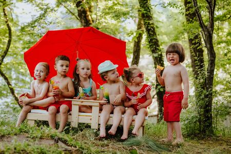 Funny toddler boy eating orange and crying while group of five children looking at him, sitting on the nature on the bench
