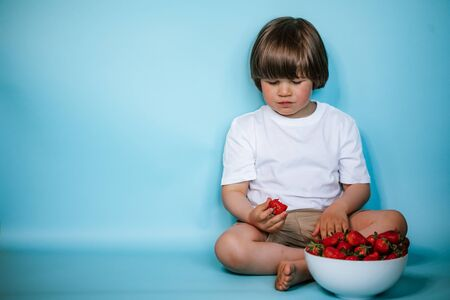 Toddler boy sitting with bowl of strawberries on the blue background