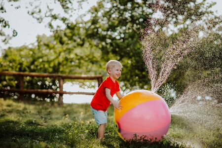 Toddler boy playing with ball sprinkler in the spring 스톡 콘텐츠 - 146695339