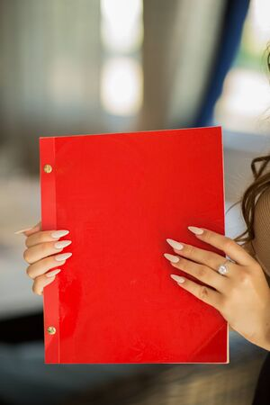 restaurant menu at womans hands with long white manicure