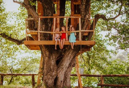 Three funny barefooted young girls in bright summer dresses playing on a tree house