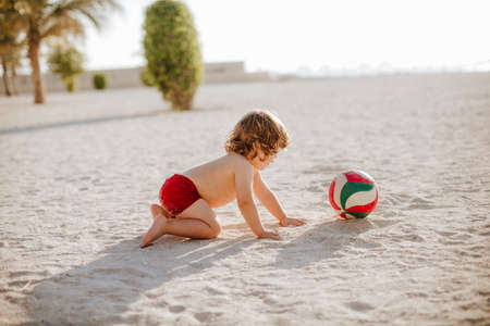 Curly toddler boy playing with ball and walking on the sea beach in the summer