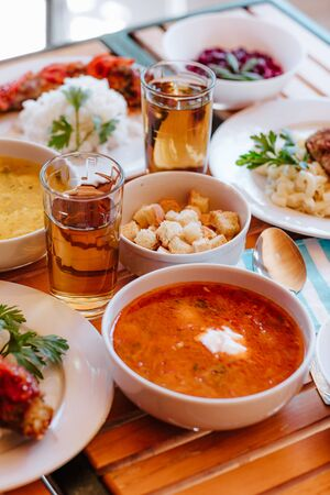 Red Ukrainian borsch with sour cream and other dishes in canteen Standard-Bild