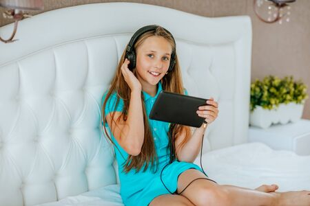 Cute young teen girl listening music at laptop