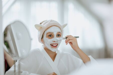 Young teen girl using creamy white mask by cosmetics brush