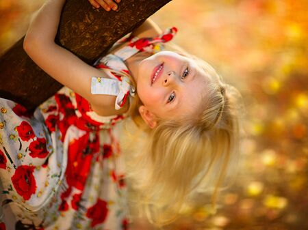 Portrait of young blond girl in poppy dress climbing a tree in the park