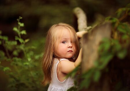 Portrait of a cute upset little girl in the park.