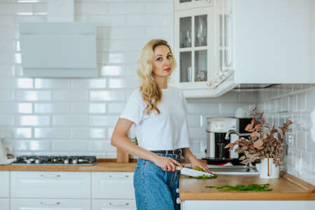 Young pretty blond woman in white summer shirt and jeans cutting fresh greenery in white kitchen. Copy space