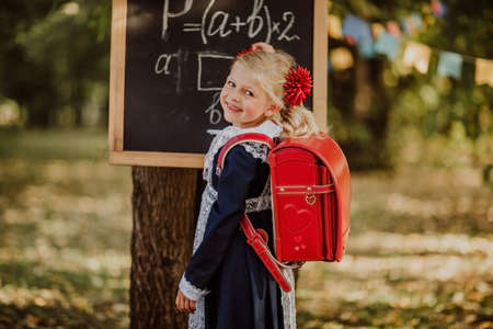 Cute young blond girl in school uniform with red school bag writing on a board by mel outdoor. Back to school. Copy space