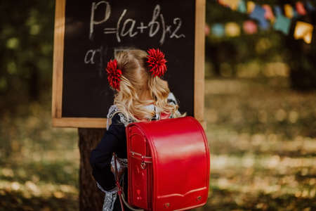 Young blond girl in school uniform with red school bag writing on a board by mel outdoor standing by her back. Back to school. Copy space