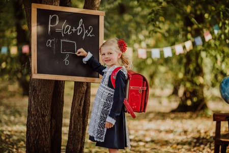 Cute young blond girl in school uniform with red school bag writing on a board by mel outdoor. Back to school. Copy space 스톡 콘텐츠