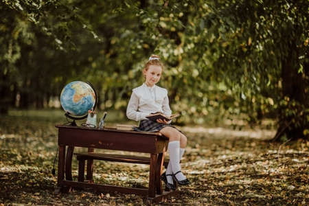 Young cute girl in white school blouse and skirt posing with a book on a wooden desk with globe and books. Back to school. Copy space 스톡 콘텐츠