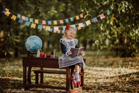 Cute young blond girl in school uniform posing near an old wooden desk with globe. Flags background. Back to school