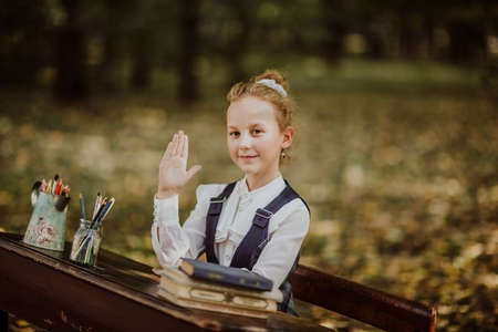 Portrait of young funny school girl sitting on a wooden desk. Hand up. Back to school. Copy space 스톡 콘텐츠