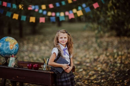Young cute blond girl in school uniform posing near an old wooden desk in the park. Back to school. Flags background